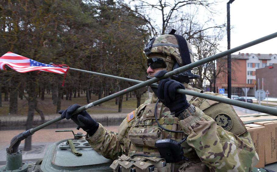 Pvt. Brandon Patel holds down the antennas on his Stryker as it passes through Alytus, Lithuania, Monday, March 23, 2015. Patel and the other soldiers of Lightning Troop, 3rd Squadron, 2nd Cavalry Regiment began their convoy, dubbed Dragoon Ride, from Alytus through Poland and the Czech Republic to their home base at Vilseck, Germany, after training in Lithuania.