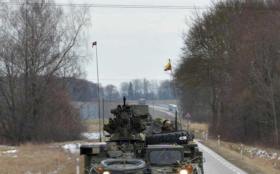 An AH-64 Apache helicopter escorts Strykers of Lightning Troop, 3rd Squadron, 2nd Cavalry Regiment as they convoy from Alytus, Lithuania, to the Polish border, Monday, March 23, 2015. They will continue their so-called Dragoon Ride through Poland and the Czech Republic to their home base at Vilseck, Germany, following training in Lithuania.