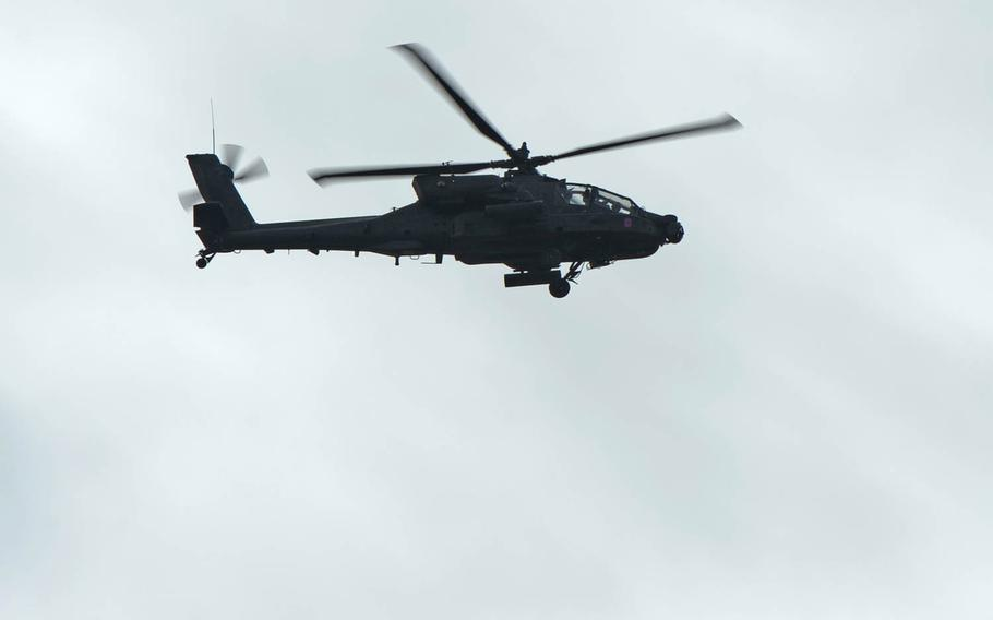 An AH-64 Apache helicopter escorts Strykers of Lightning Troop, 3rd Squadron, 2nd Cavalry Regiment as they convoy from Alytus, Lithuania, to the Polish border, Monday, March 23, 2015.