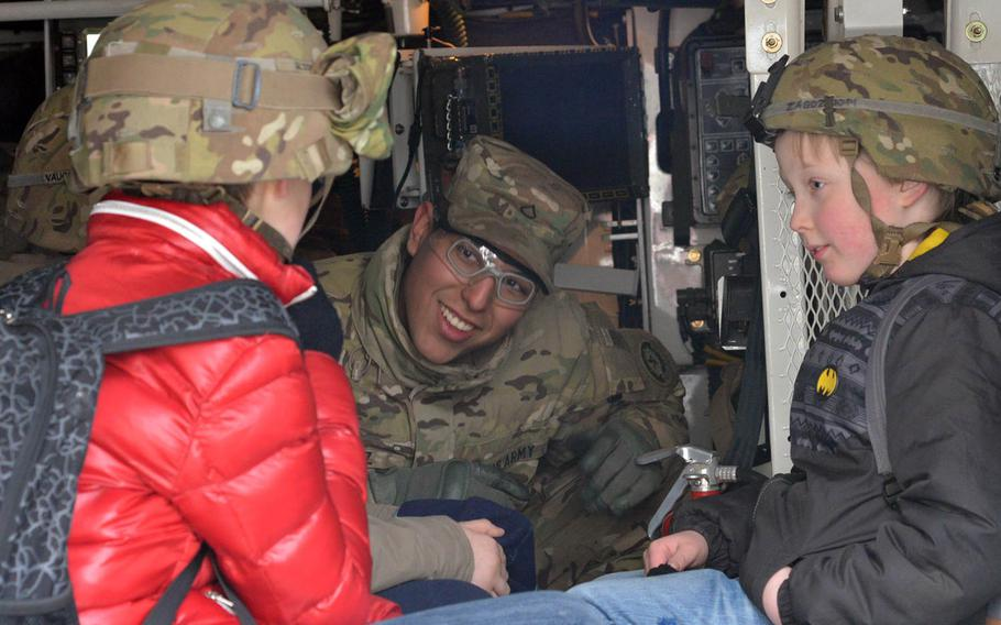 Pfc. Luis Diaz of Iron Troop, 3rd Squadron, 2nd Cavalry Regiment talks to two children decked out in U.S. Army helmets during a static display of the unit's Strykers in Panevezys, Lithuania, Monday, March 23, 2015. The soldiers of Iron Troop made a stop in downtown Panevezys during their convoy back to their home base in Vilseck, Germany, as part of the so-called Dragoon Ride, after training in Estonia.