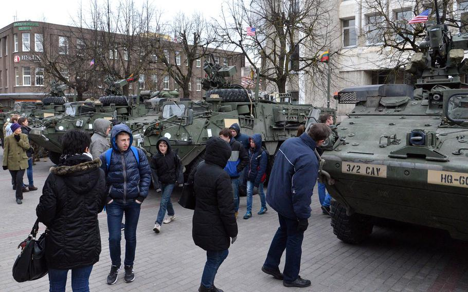 People check out the Strykers of Iron Troop, 3rd Squadron, 2nd Cavalry Regiment during a static display of the unit's Strykers in downtown Panevezys, Lithuania, Monday, March 23, 2015. The soldiers of Iron Troop made a stop in Panevezys during their convoy back to their home base in Vilseck, Germany, as part of the so-called Dragoon Ride, after training in Estonia.