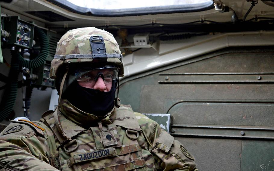Spc. John Zagozdon of Iron Troop, 3rd Squadron, 2nd Cavalry Regiment talks about training in Estonia and the convoy from there back to Vilseck, Germany, during a fuel stop in Lithuania, Monday, March 23, 2015.