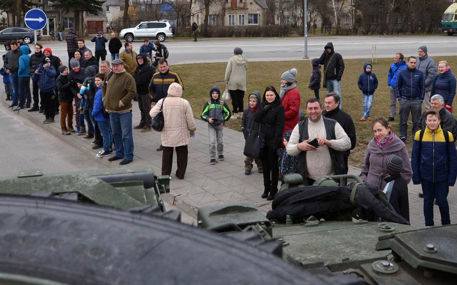 Spectators line the street on the outskirts of Panevezys, Lithuania, to see the Strykers of Iron Troop, 3rd Squadron, 2nd Cavalry Regiment, Monday, March 23, 2015. The soldiers of Iron Troop made a stop in Panevezys during their convoy back to their home base in Vilseck, Germany, as part of the so-called Dragoon Ride, after training in Estonia.