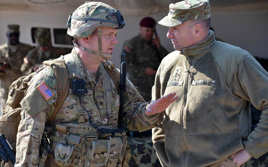 Col. Michael Foster, commander of the 173rd Airborne Brigade, left, talks to U.S. Army Europe commander Lt. Gen. Ben Hodges after Foster and other soldiers of his unit  jumped into the Smardan training center, Romania, Tuesday, March 24, 2015.