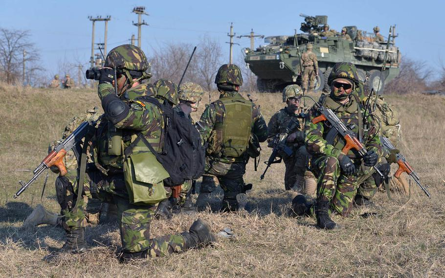 Romanian soldiers keep watch after meeting up with soldiers from the 173rd Airborne Brigade who had parachuted in earlier, as a Stryker of 2nd Squadron, 2nd Cavalry Regiment rolls into the Smardan training center, Romania, Tuesday, March 24, 2015.