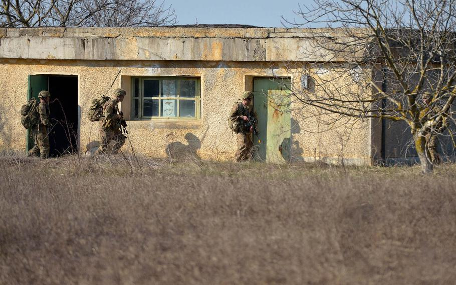 Soldiers of the 173rd Airborne Brigade clear a house after parachuting into the Smardan training center, Romania, Tuesday, March 24, 2015.
