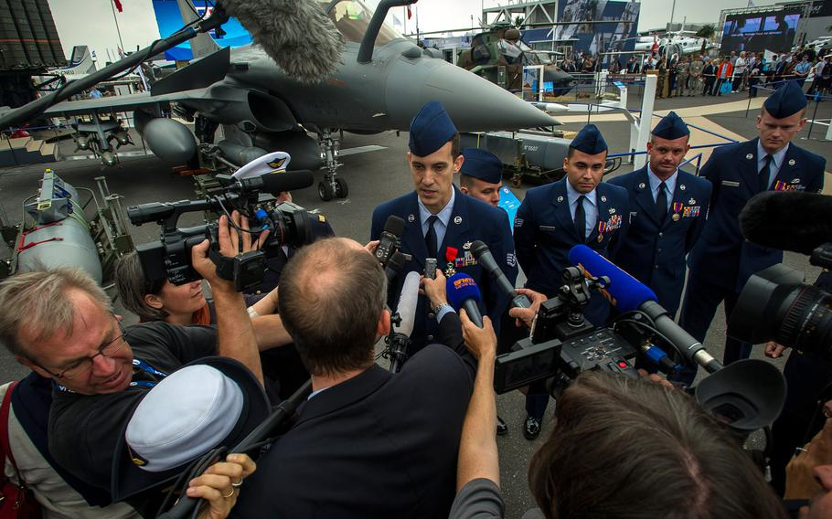 Staff Sgt. Greggory Swarz speaks to French media after being awarded the French Legion of Honor at Le Bourget Airport during the International Paris Air Show on Monday, June 15, 2015. Swarz helped to save three French airmen after a Greek F-16 Fighting Falcon crashed into the parking ramp at Los Llanos Air Base, Spain.