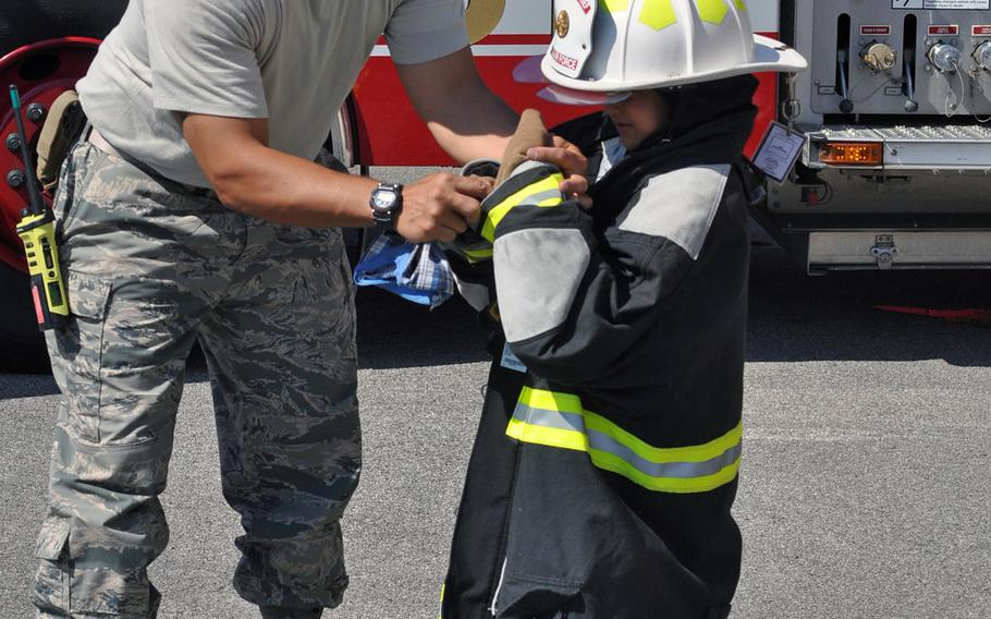 Master Sgt. Angus Adolpho, Aviano assistant fire chief, helps a visitor try on a fire suit during a tour of Aviano Air Base's fire department, Friday, July 10, 2015.
