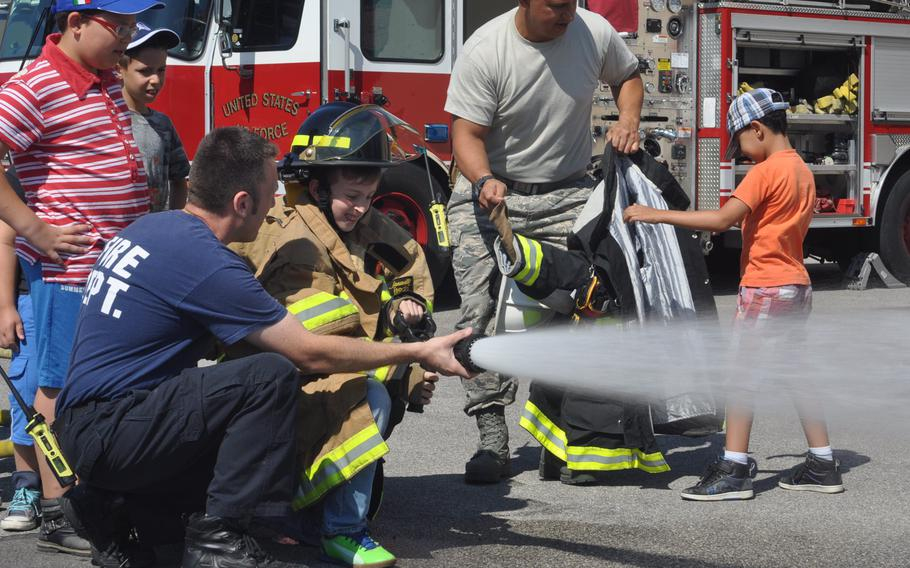 Mateo Copetti, an Italian fire fighter at Aviano Air Base, assists a young visitor sprayer water from a fire engine's hose Friday, July 10, 2015, during a tour of the base in Italy.