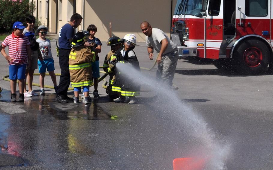 A group of Italian children from Porcia, Italy, watch as a one of them strikes down a cone at Aviano Air Base's fire department on Friday, July 10, 2015.