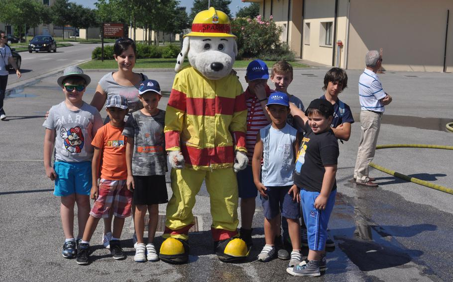 Sparky poses with a group of children touring Aviano Air Base, Italy on Friday, July 10, 2015.