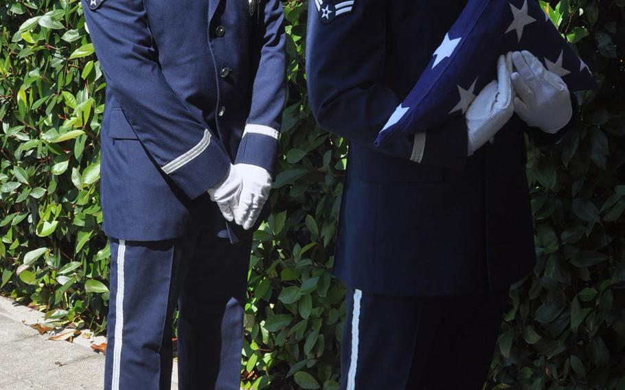 Airman 1st Class Roger Lanoie holds the flag while fellow 31st Fighter Wing Honor Guard member Senior Airman Joshua Sharer stands by during a flag-folding demonstration to visitors at Aviano Air Base, Italy, Friday, July 10, 2015.