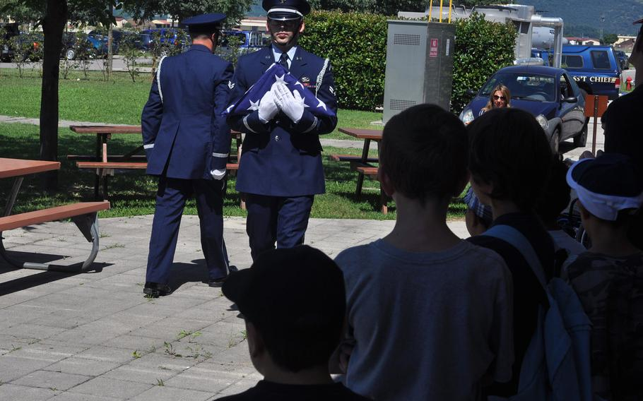 Airman 1st Class Roger Lanoie and fellow 31st Fighter Wing Honor Guard member Senior Airman Joshua Sharer give a flag-folding demonstration to a group visiting Aviano Air Base, Italy on Friday, July 10, 2015.