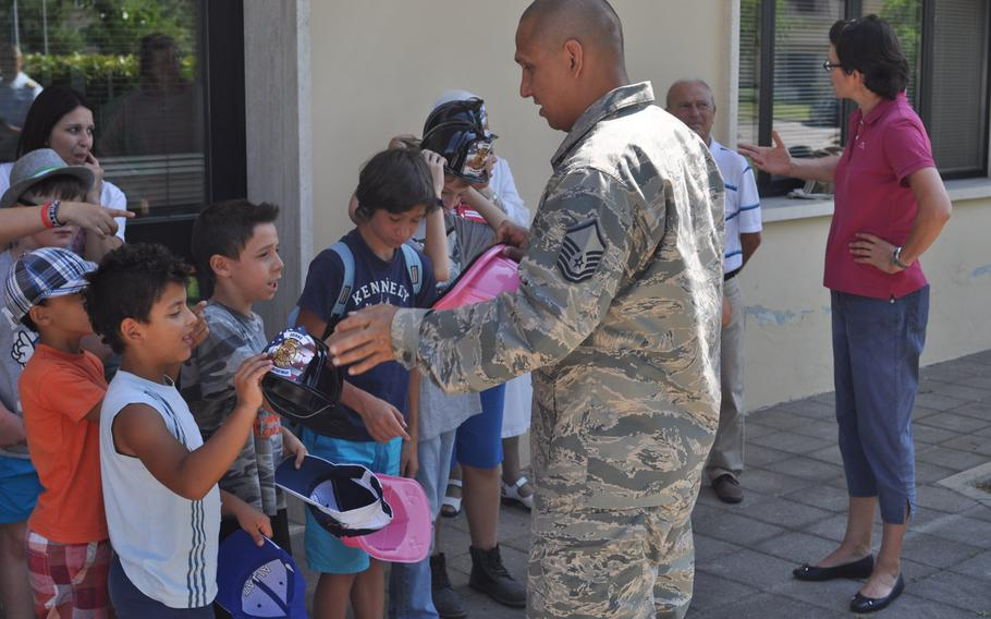 Master Sgt. Angus Adolpho, Aviano assistant fire chief, hands out fire engine hats to children from Porcia, Italy, during a tour of Aviano Air Base's fire department, Friday, July 10, 2015.