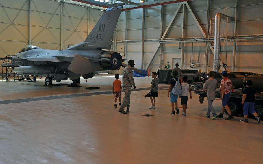 A group of visitors enters the hanger to view an F-16 Fighting Falcon provided by the 31st Fighter Wing's 510th Fighter Squadron, Friday, July 10, 2015, during a tour of Aviano Air Base, Italy.