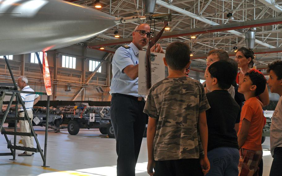 ITAF Technical Sergeant Zecca Stefano explains a few aspects of an F-16 Fighting Falcon on display Friday, July 10, 2015, at Aviano Air Base, Italy.