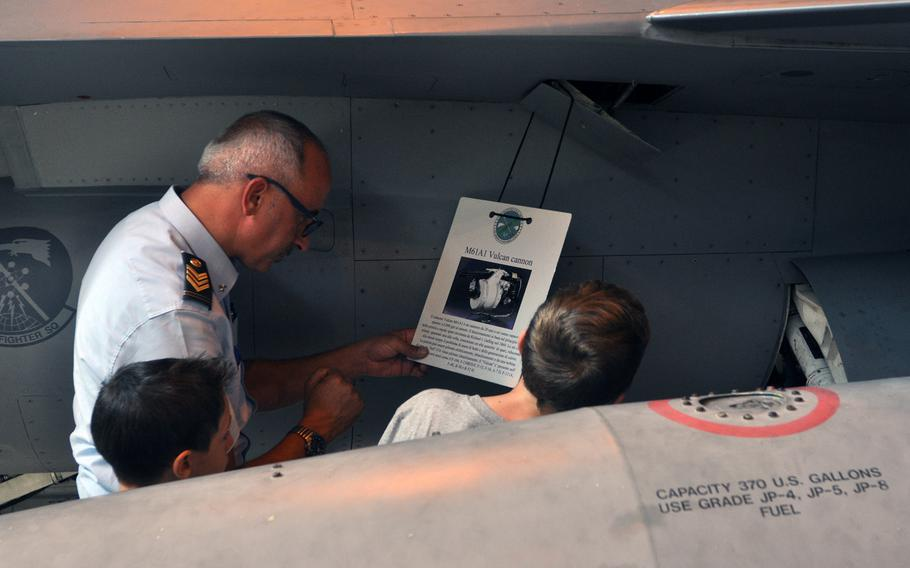 ITAF Technical Sergeant Zecca Stefano reads the information card of an F-16 Fighting Falcon's Volcan Cannon on display Friday, July 10, 2015, at Aviano Air Base, Italy.
