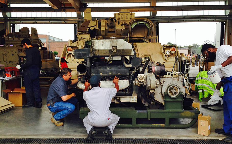 Mechanics work on the engine of a U.S. Army Bradley Fighting Vehicle in a motor pool at Coleman Barracks in Mannheim, Germany, Tuesday, Sept. 1, 2015.