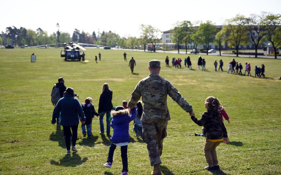 A soldier brings his kids to see a UH-60 Black Hawk helicopter during a Science Technology Engineering and Math activity on base, at Grafenwoehr, Germany, Tuesday, April 30, 2019.