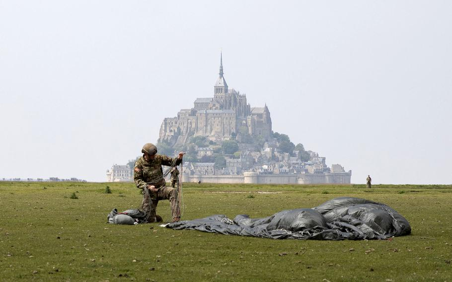 A paratrooper from the 10th Special Forces Group (Airborne) packs his parachute near the island of Mont Saint Michel, France, on Saturday, May 18, 2019.