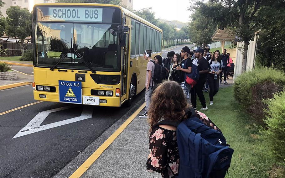High school students wait for the school bus in the Ikego housing area near Yokosuka Naval Base, Japan, Monday, Aug. 27, 2018.