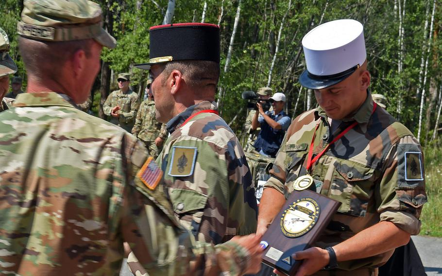 The French Foreign Legion sniper team accepts their plaque and awards from U.S. Army Sgt. 1st Class Jason Sypherd during the 2019 European Best Sniper Team Competition, at Grafenwoehr, Germany, Thursday, July 25, 2019.