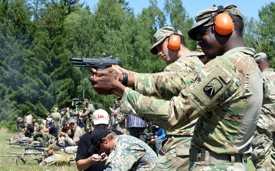 U.S. soldiers fire different handguns during the European Best Sniper Team Competition, at Grafenwoehr, Germany, Thursday, July 25, 2019.