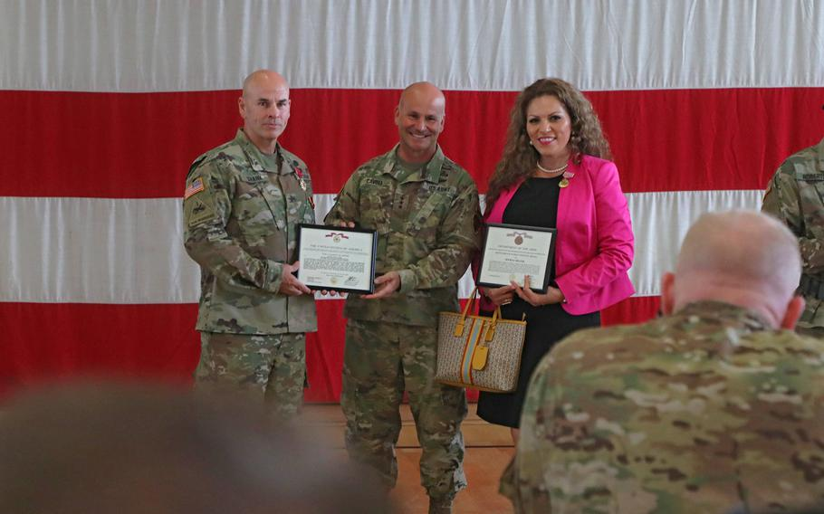 Col. David Shank, center, and his wife Myrna receive awards from Lt. Gen. Christopher Cavoli before the 10th Army Air and Missile Defense Command change of command ceremony at the Kleber Kaserne gym in Kaiserslautern, Germany, Aug. 7, 2019. Shank received the Legion of Merit award and his wife received the Meritorious Public Service Medal for her service to the 10th Army Air and Missile Defense Command community.