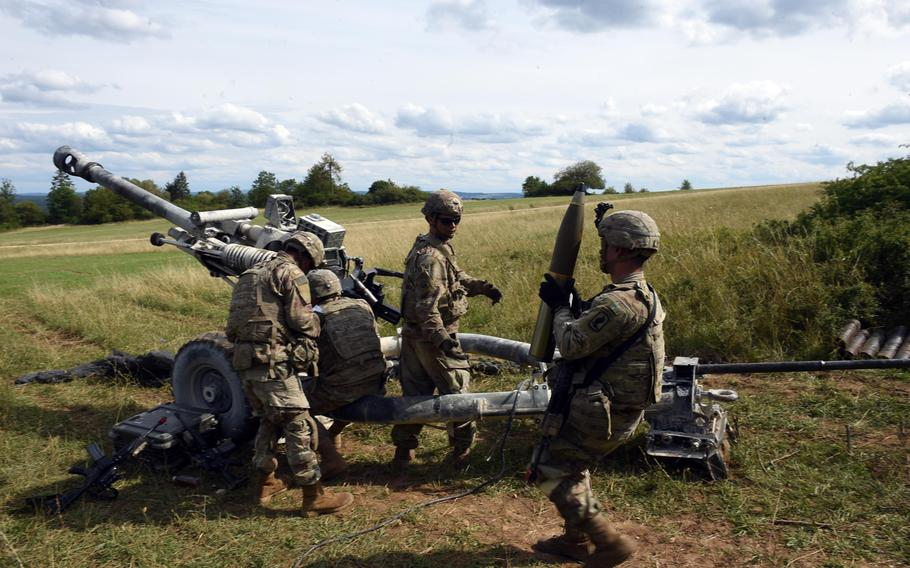 A soldier brings a 105mm artillery shell to an M119-A3 howitzer during an exercise in Grafenwoehr, Germany, Aug. 13, 2019.