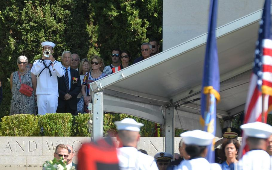 A U.S. Navy bugler plays taps at the foot of the chapel monument at Rhone American Cemetery in Draguignan, France, at the ceremony marking the 75th anniversary of Operation Dragoon, Friday, Aug. 16, 2019.