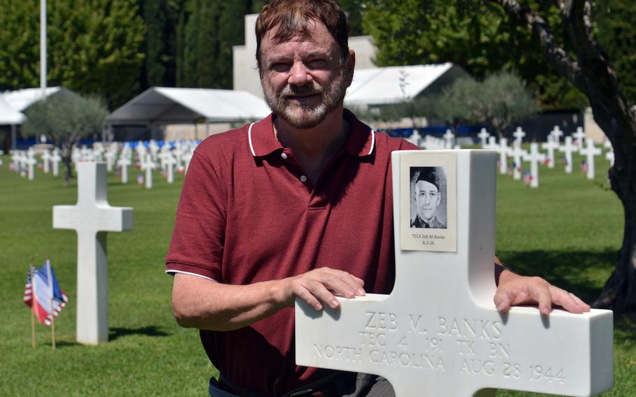 Steven Hill poses next to the grave of his uncle, Tech. 4 Zeb Murphy Banks, at Rhone American Cemetery in Draguignan, France, Thursday, Aug. 15, 2019. Banks was an Army tanker who was killed Aug. 28, 1944, when his tank hit a mine. Hill came to the cemetery to attend Friday's ceremony marking the 75th anniversary of Operation Dragoon.