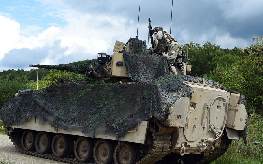 A Bosnian soldier throws a mock grenade inside a Bradley Fighting Vehicle during exercise Combined Resolve at Hohenfels, Germany, Monday, Aug. 19, 2019.