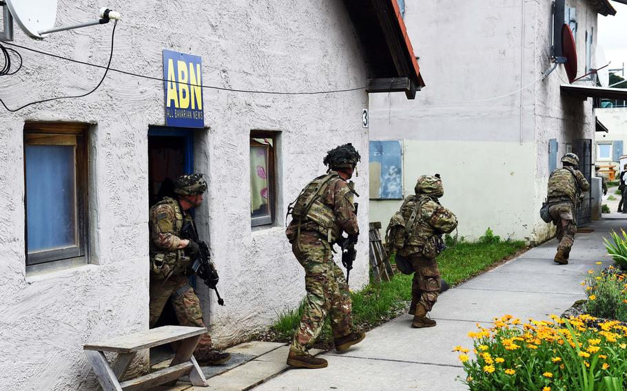 """Soldiers with the 1st Infantry Division's 1st Armored Brigade Combat Team exit a building to engage """"enemy forces"""" during exercise Combined Resolve at Hohenfels, Germany, Monday, Aug. 19, 2019."""