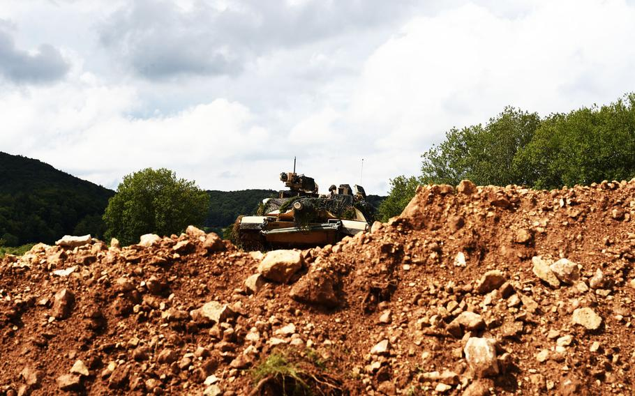 An M1A2 Abrams tank peers out from behind a defensive position during exercise Combined Resolve at Hohenfels, Germany, Monday, Aug. 19, 2019.