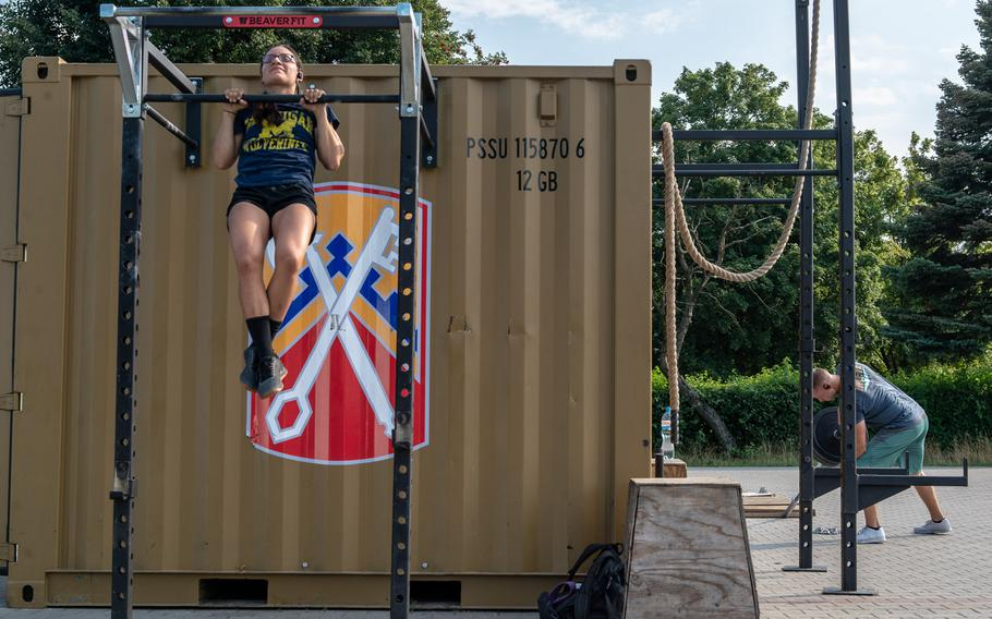 Sgt. Lauren Meza does pullups while Maj.Joshua Rookus lifts weights on a military base in Powidz, Poland, Aug. 27, 2019. The soldiers deployed to the base are on rotations lasting up to nine months.