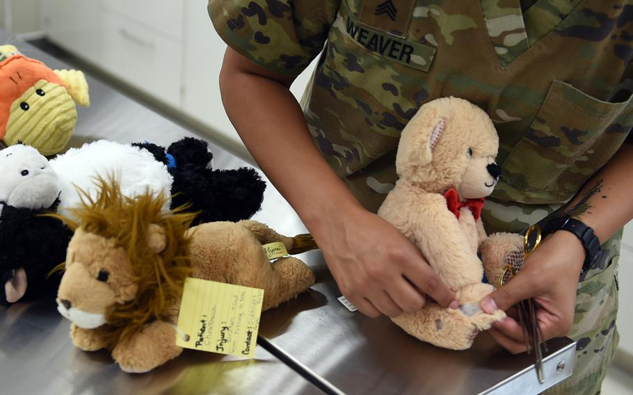 A stuffed bear's wound is displayed on the operating table at the teddy bear suture clinic in Vilseck, Germany, Wednesday, Aug. 28, 2019. Army veterinary technicians at the clinic practiced stitching up wounds on all types of stuffed animals, not just teddy bears.