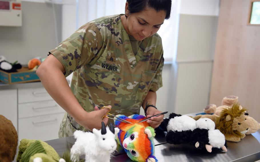 """Sgt. Toni Weaver, an animal care technician at Rose Barracks, operates on her patient, """"Rainbow Kitty,"""" at a clinic for stuffed animals in Vilseck, Germany, Wednesday, Aug. 28, 2019."""
