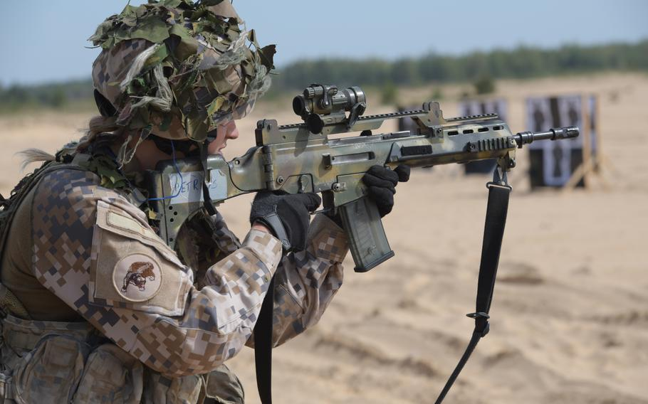 A Latvian soldier fires her rifle from the standing position during the ?live-fire? event of the Best Infantry Squad Competition, Aug. 28, 2019, in Rukla, Lithuania.
