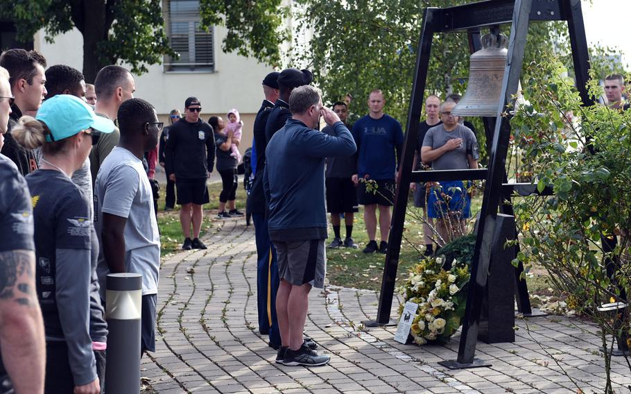 """The former commander of the """"Big Windy,"""" Craig Wilhelm, center, salutes the memorial to the crew of the Windy 25 flight at Ansbach, Germany, on Sept. 6, 2019, as soldiers with the Army's 12th Combat Aviation Brigade stand at attention during the playing of taps, before the Windy 25 5K race."""