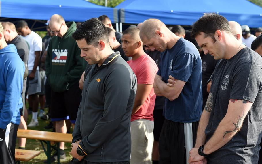 Soldiers, veterans and families lower their heads as a chaplain says a prayer before the Windy 25 5K run at Ansbach, Germany, Sept. 6, 2019. The race memorializes those who died in the Windy 25 helicopter crash in Afghanistan in 2005 and raises money for families who have lost loved ones in the military.
