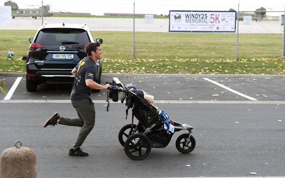 """Capt. Cody Omilusik, the commander of """"Big Windy,"""" runs with a baby in a jogging stroller during the Windy 25 5K memorial run at Ansbach, Germany, Sept. 6, 2019."""