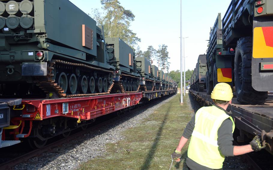 A railyard worker walks past a  row of M270-A1 MLRS rocket launch systems that arrived in Grafenwoehr, Germany, Wednesday, Sept. 11, 2019.