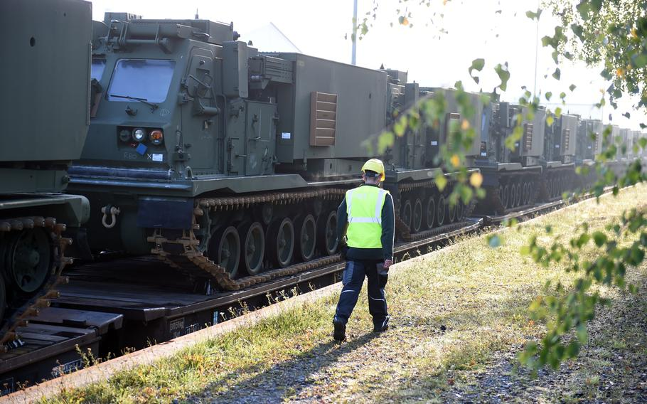 A railyard worker walks past a  row of M270-A1 MLRS rocket launch systems that arrivied on a train in Grafenwoehr, Germany, Wednesday, Sept. 11, 2019.