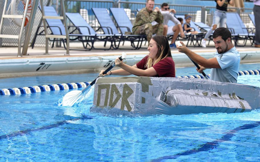 Savannah Inman and Brandon Garneau with the 31st Fighter Wing's outdoor recreation department at Aviano Air Base, Italy, on their way to winning the first cardboard boat race to be held at the base on Sept. 19, 2019.