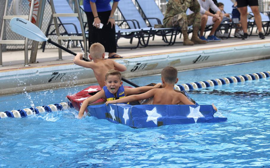 Five-year-old Zachary Odom, center, his brother Asher, 8, left, and a friend compete in the first cardboard boat race to be held at Aviano Air Base in Italy on Sept. 19, 2019. The boys received a trophy for having the most creative boat.
