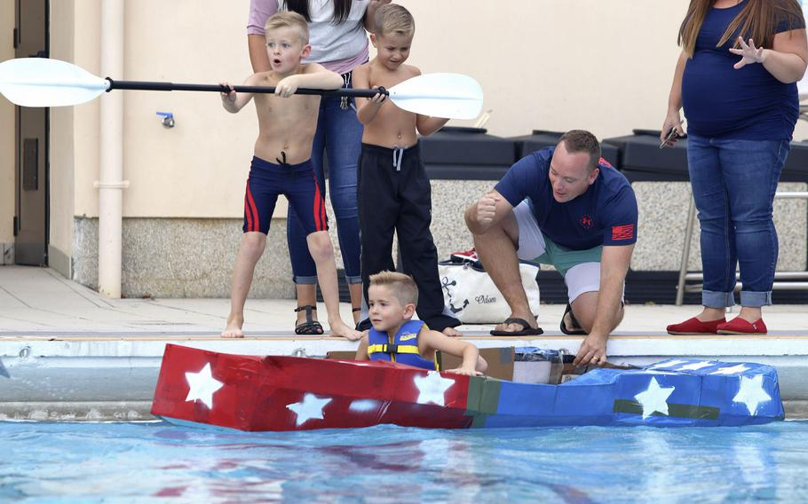 Zachary Odom, 5, takes a seat inside a cardboard boat at the cardboard boat race, held at Aviano Air Base in Italy, Sept. 19, 2019.