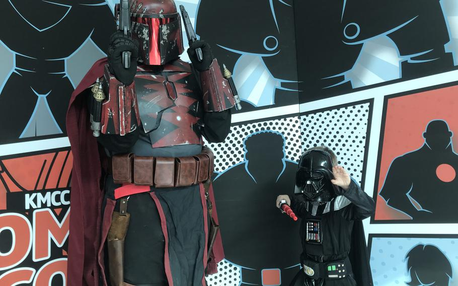 Logan Hinton, 31, dressed as a Mandalorian from the ''Star Wars'' galaxy and son Silas, 4, dressed as Darth Vader, pose together in front of a KMCC Comic Con backdrop during an event for comic book and other costumed fans at the Ramstein main exchange on Sunday, Sept.22, 2019.
