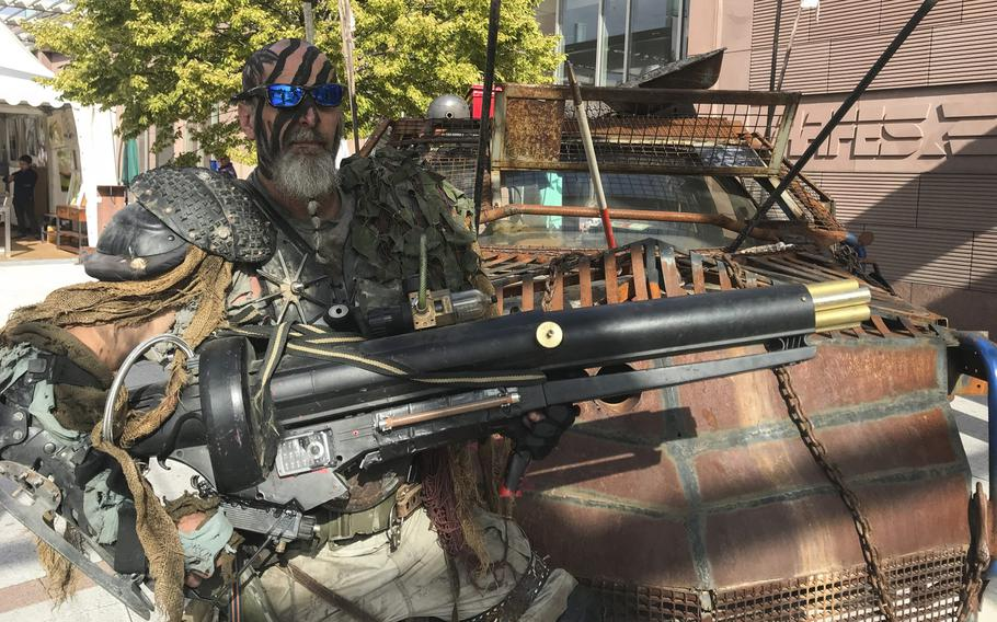 Dressed as a post-apocalyptic warrior, Brian Sachs, 54, poses for a photo in front of his ''Mad Max: Fury Road''-inspired automobile in front of the Ramstein main exchange on Sunday, Sept.22, 2019. Sachs helped organize the mall's KMCC Comic Con event to celebrate the shopping center's 10-year anniversary and the opening of a new comic shop.