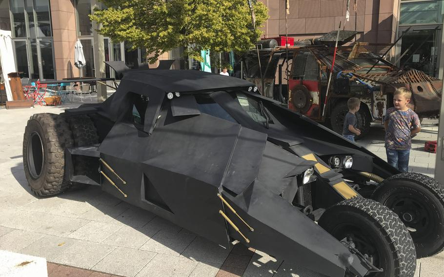Children check out Air Force veteran Brian Sachs's movie-inspired autos on display at the Ramstein main exchange on Sunday, Sept.22, 2019, duirng the KMCC Comic Con event.