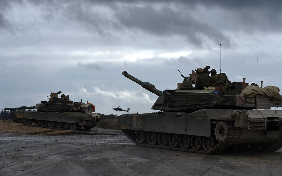 U.S. Army M1A2 Abrams tanks and an AH-64 Apache helicopter are ready to attack an  enemy position during a live-fire exercise at Grafenwoehr, Germany in 2018. The Army will deploy a division headquarters, three tank brigades and scores of other troops to Europe early next year for what will be the largest American-led war game on the Continent in 25 years, U.S. European Command said Monday, Oct. 7, 2019.